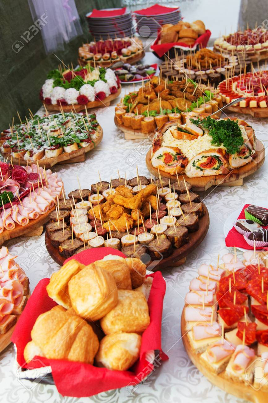 table with mix of different finger food snacks for a party stock