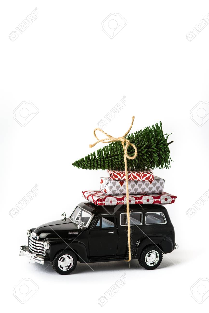 Driving Home For Christmas.A Black Toy Car With Presents And A Christmas Tree On Top Of