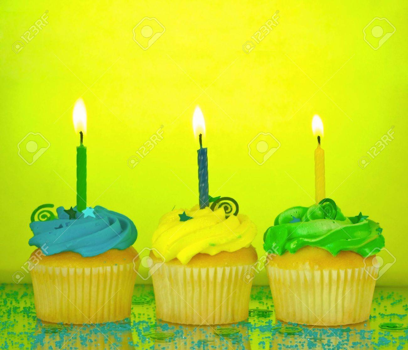 Three Birthday Cupcakes In Blue Green And Yellow With Lit Candles