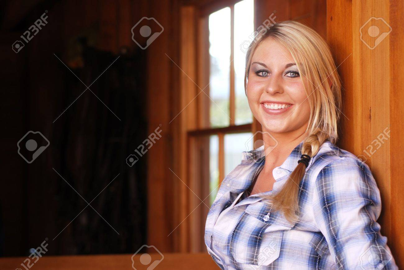 Young adult blonde woman inside a stable on a country farm Stock Photo - 3654761
