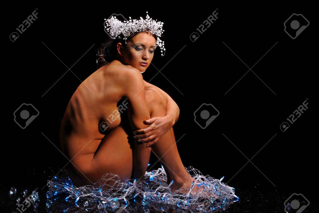 Nude woman surrounded by snow and Christmas lights on black background Stock Photo - 4861451
