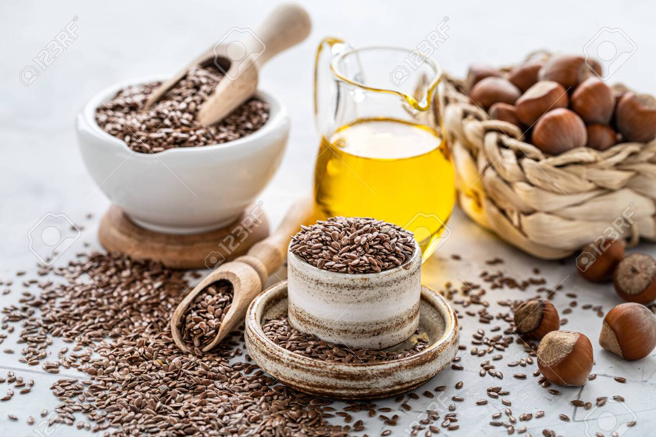 Walnut and flaxseed oil in a bottle and ceramic bowl with brown flax seeds and a wooden spoon on a white background. - 136982415