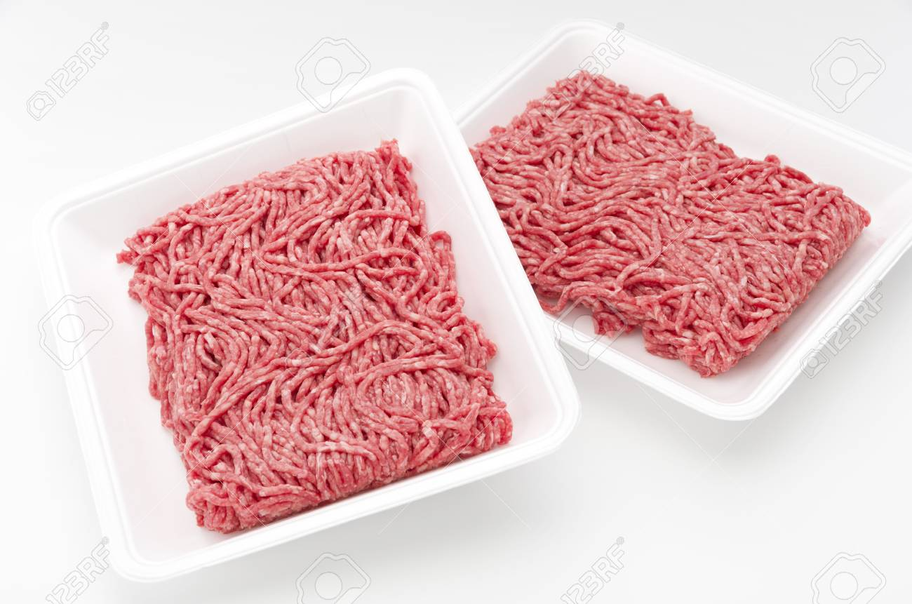 Raw beef minced meat in a white polystyrene tray isolated on a white background. - 68517311