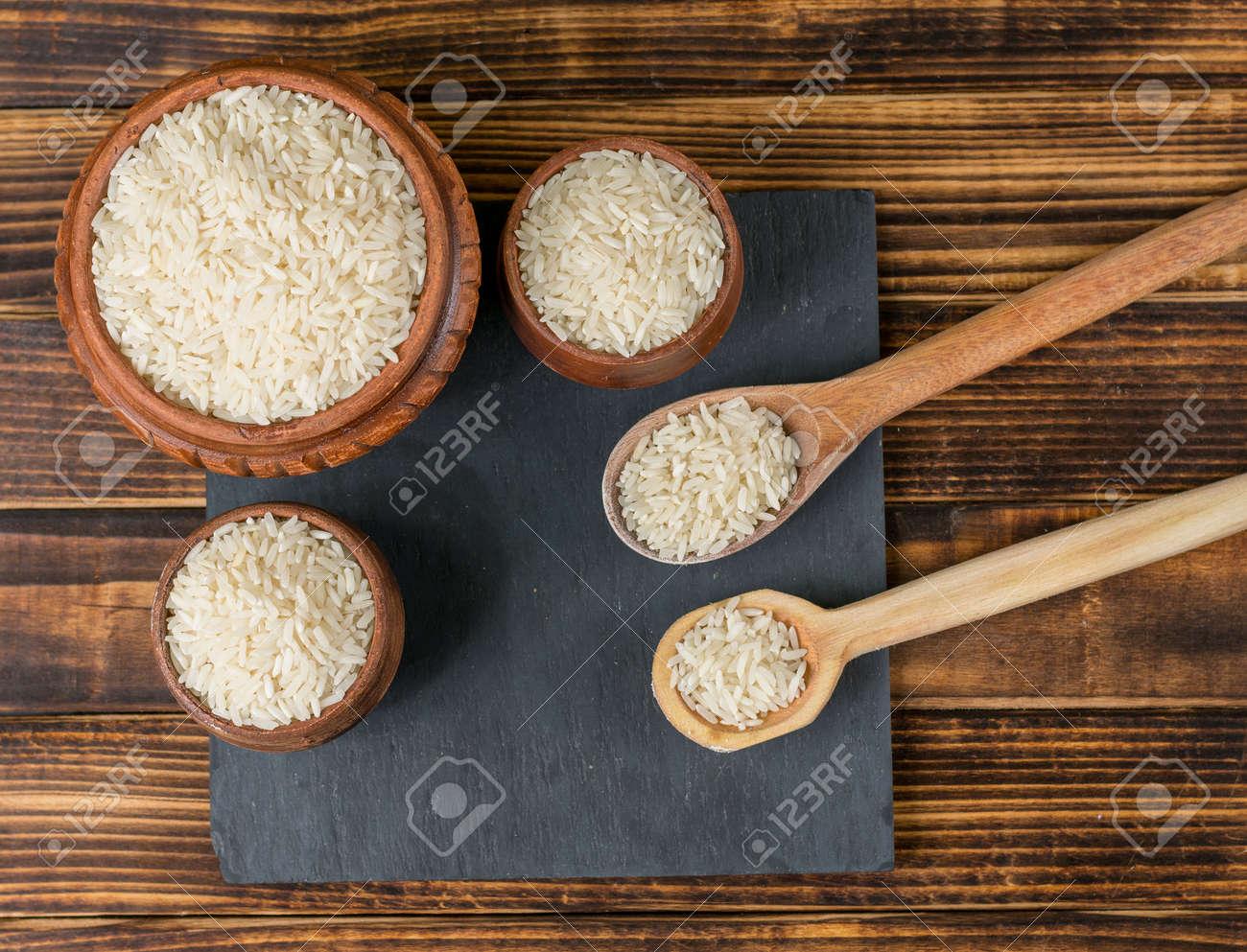 Uncooked rice over kitchen utensils and dark wood - 151833952