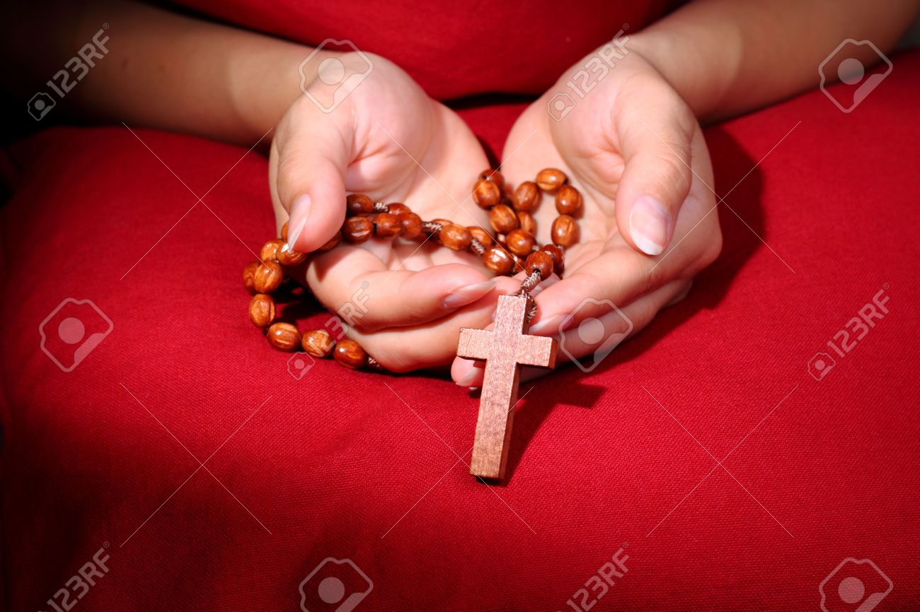Female hands holding wooden rosary with cross on red background Stock Photo - 7126220