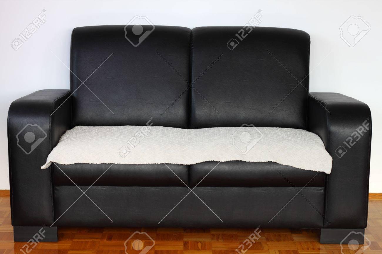 Black leather modern sofa on hardwood against white wall