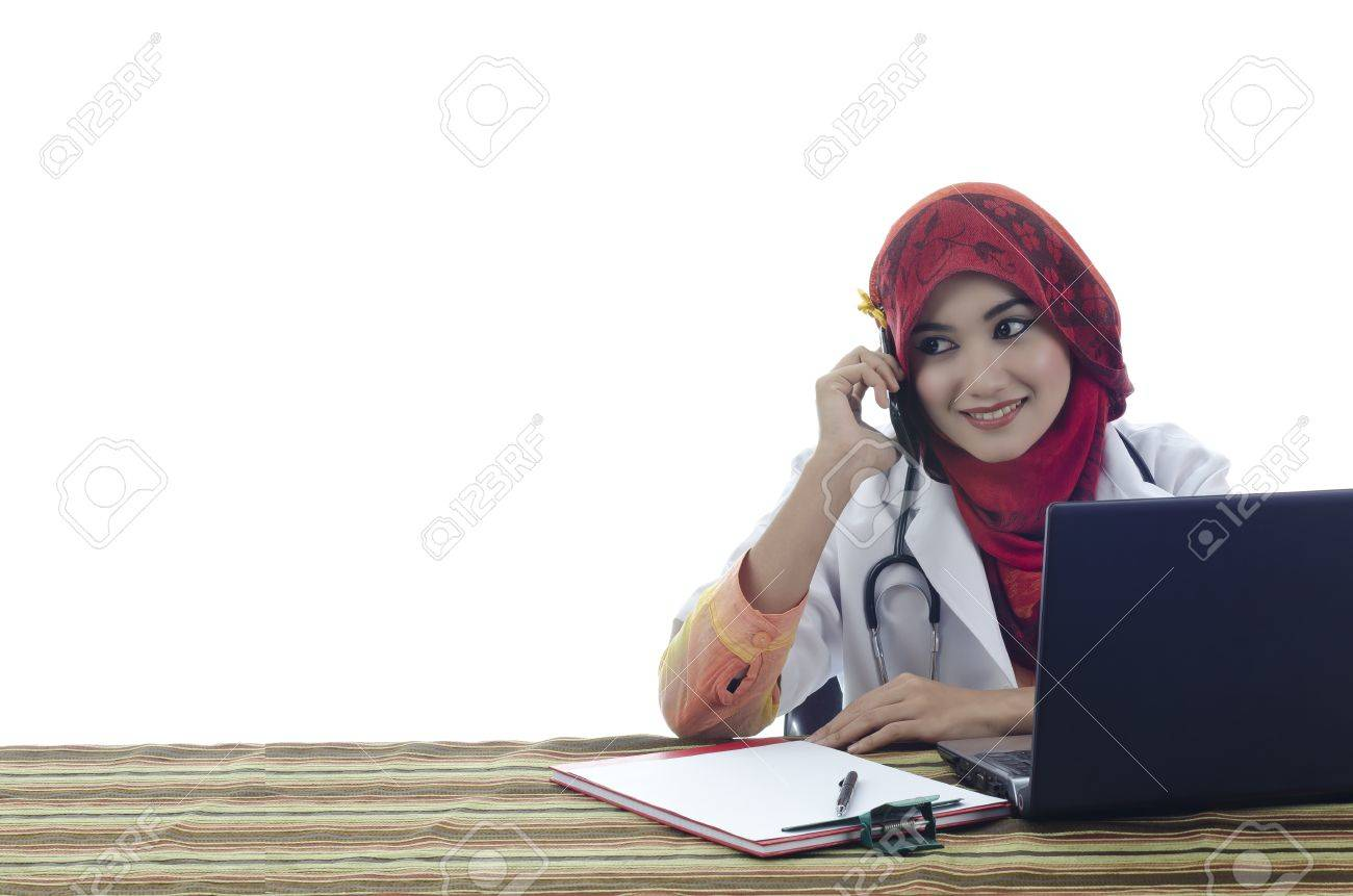 beautiful young muslim woman doctor with stylish head scarf make a phone call in front of laptop isolated on white background Stock Photo - 11904882