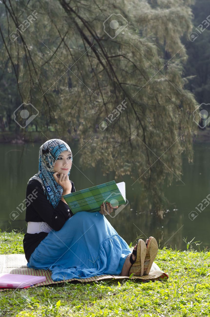 beautiful young muslimah woman with head scarf thinking while reading a book near the lake Stock Photo - 12233076