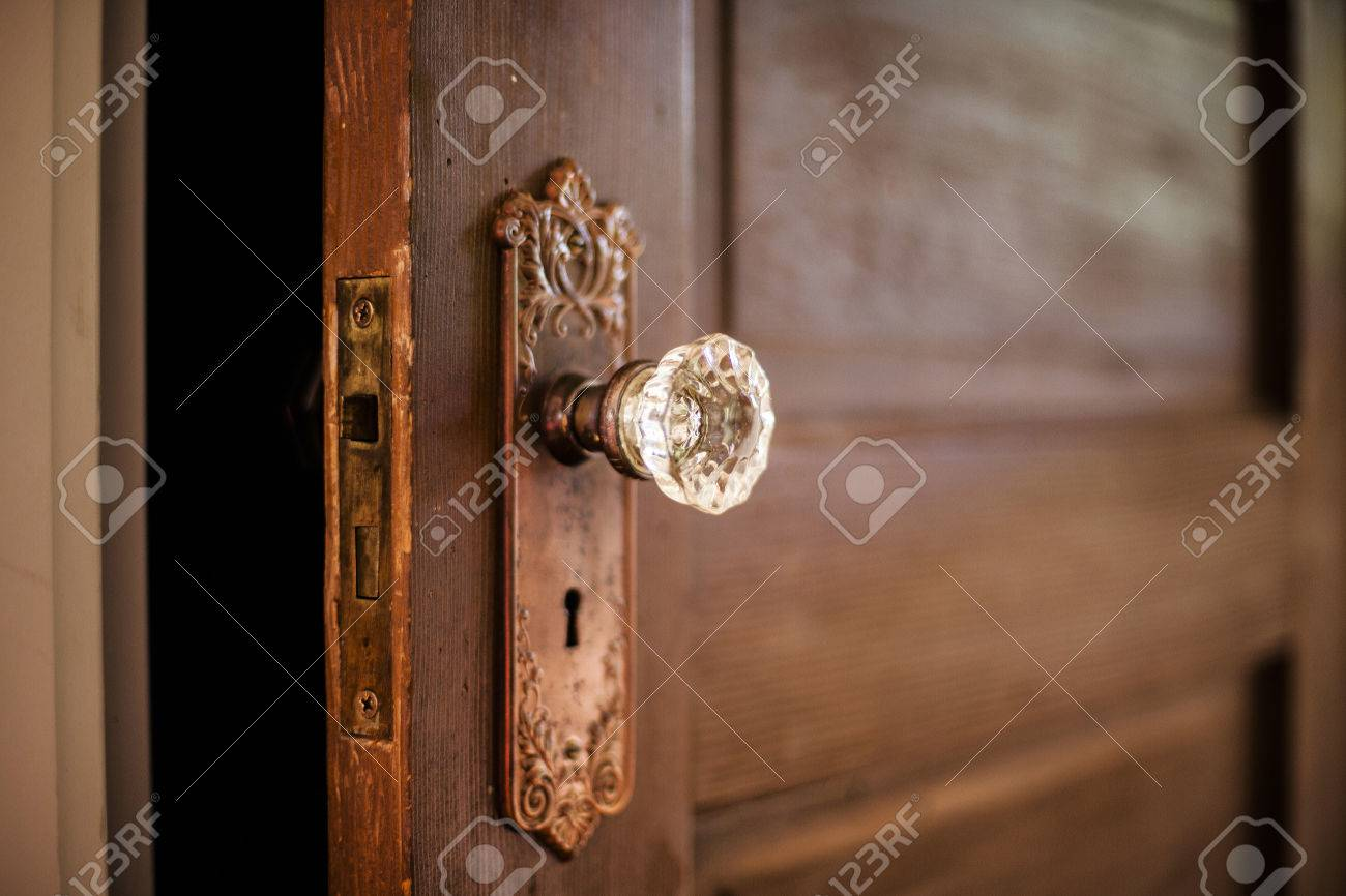 A Weathered Old Wooden Door With An Ornate Crystal Door Knob. Stock ...