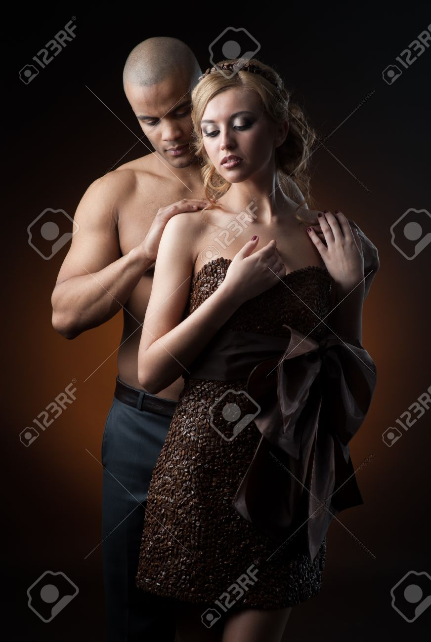 young sensual caucasian woman in dress made of coffee beans and black man standing over gradient orange background Stock Photo - 17891238