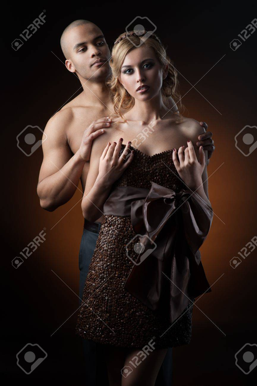 young sensual caucasian woman in dress made of coffee beans and black man standing over gradient orange background - 18626642