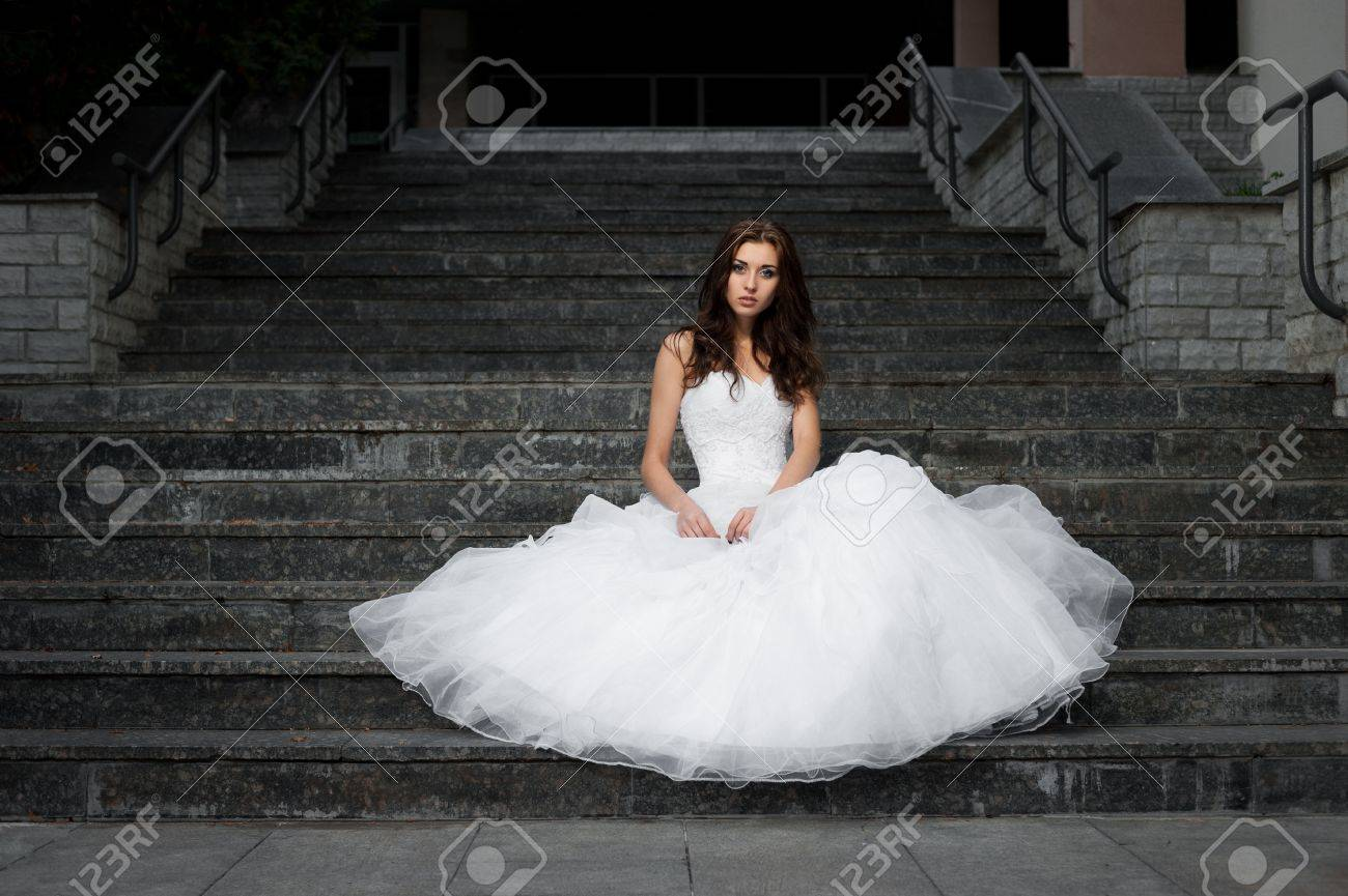 outdoors portrait of beautiful young caucasian brunette woman in white wedding dress over gray stairs on background - 18793608