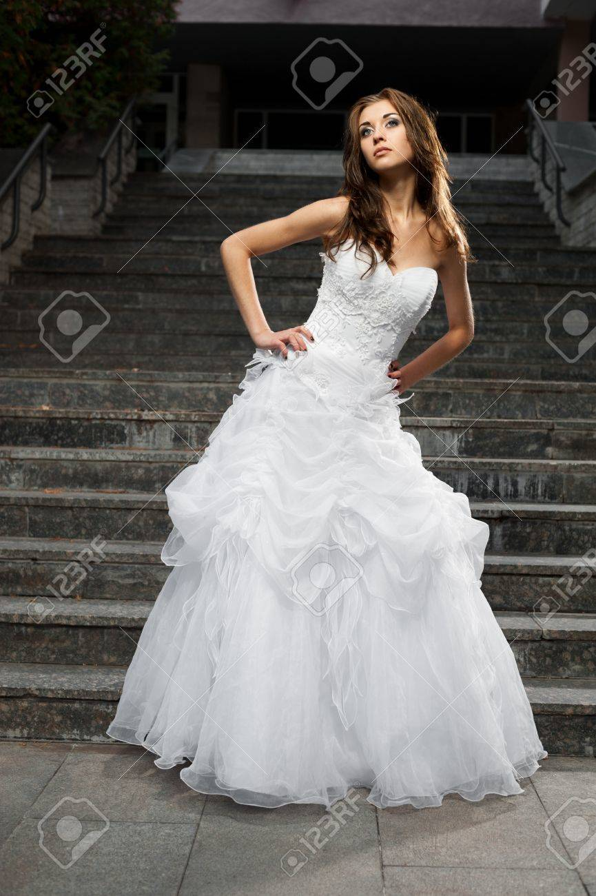 outdoors portrait of beautiful young caucasian brunette woman in white wedding dress over gray stairs on background Stock Photo - 18793616