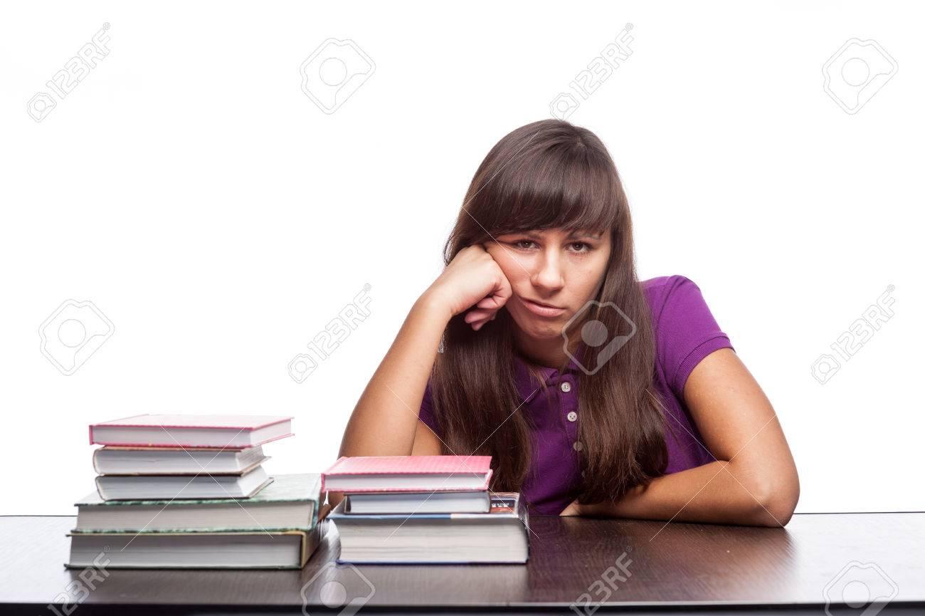 foto de archivo caucsico chica aburrido sentado en el escritorio con libros aislados en blanco