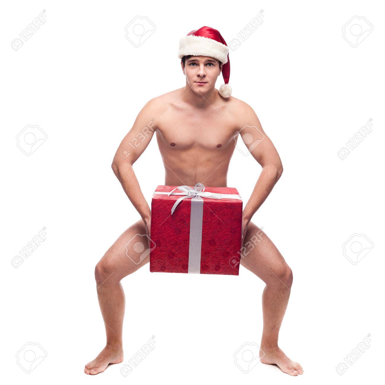 pere noel nu Gaie Nu Jeune Homme En Chapeau De Père Noël Tenant Gros Cadeau  pere noel nu