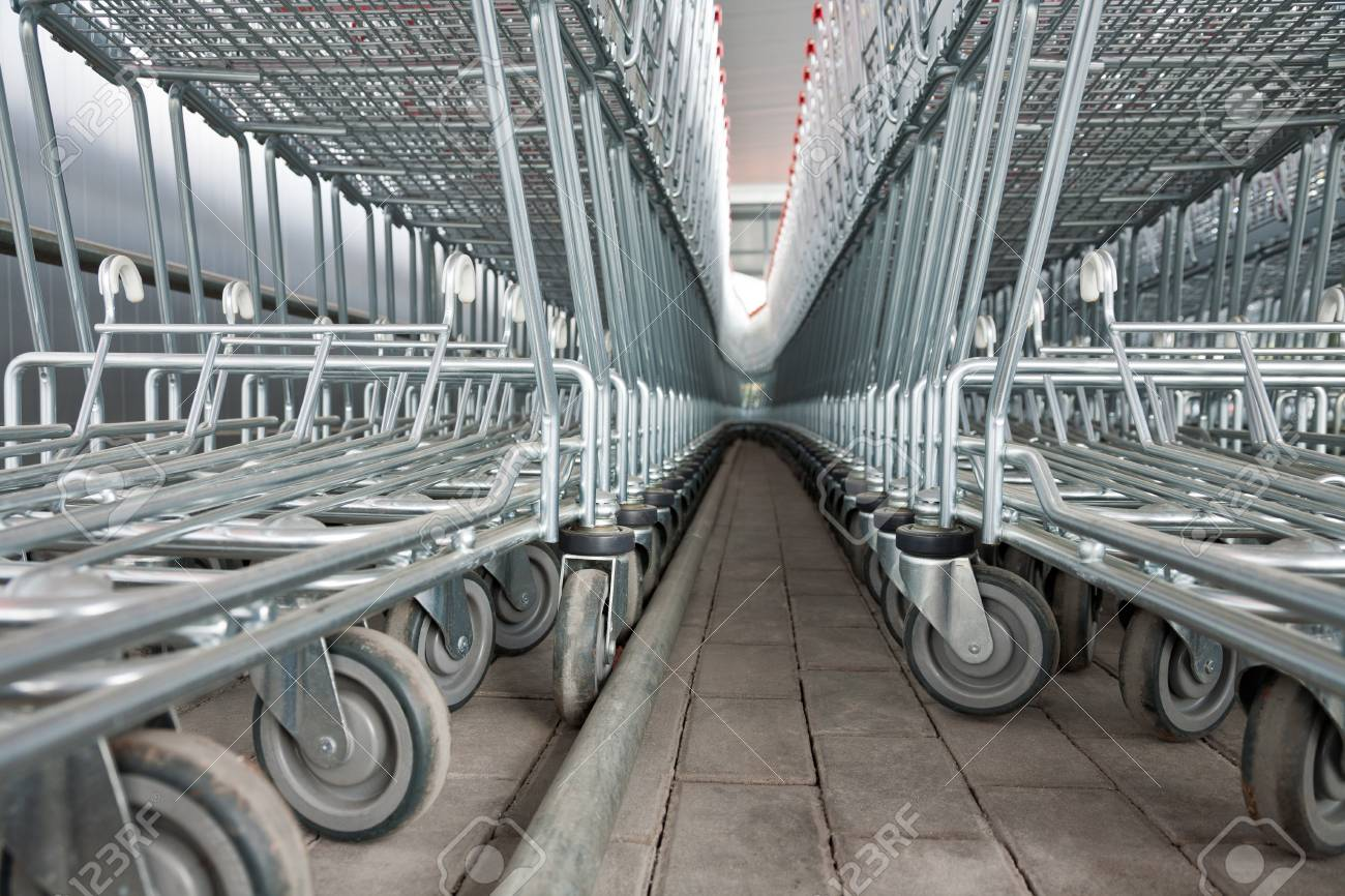 Rows of empty metal shopping carts in a supermarket Stock Photo - 18342349
