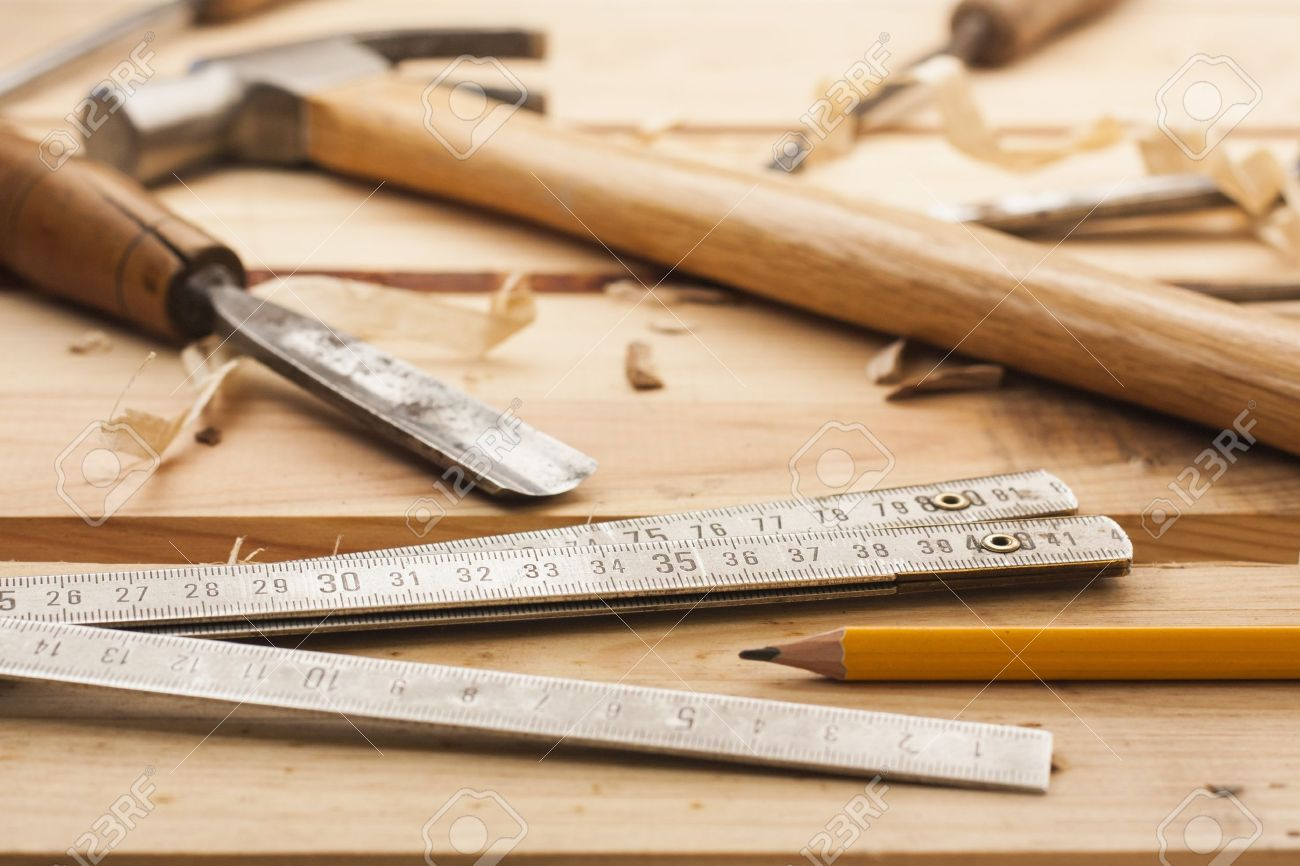 Carpenter Tools Hammer Meter Chisel And Shavings Over Wood Table