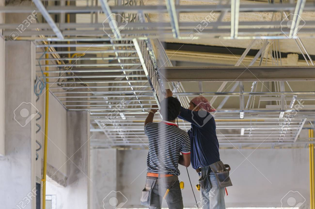 Construction worker ceiling metal frame with screwdriver for interior build gypsum board ceiling - 93528055
