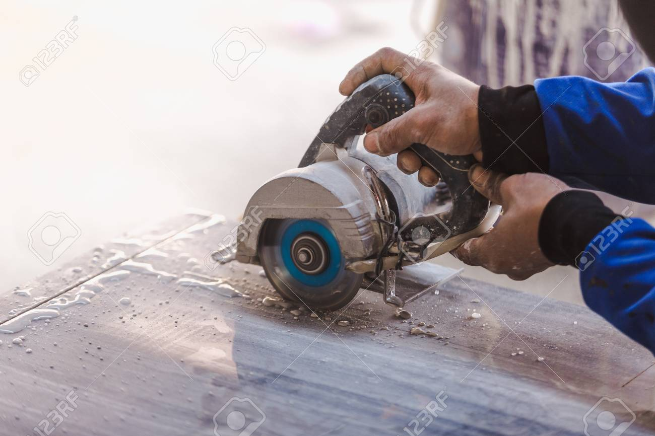 Man professional worker cutting tile with circular saw electric construction interior. - 94230524