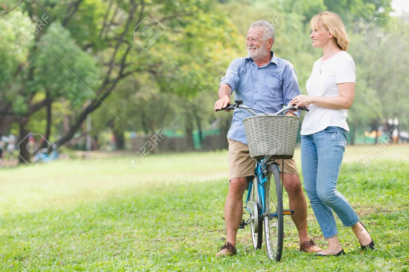 Senior couple walking their bike along happily talking happily. - 95754907
