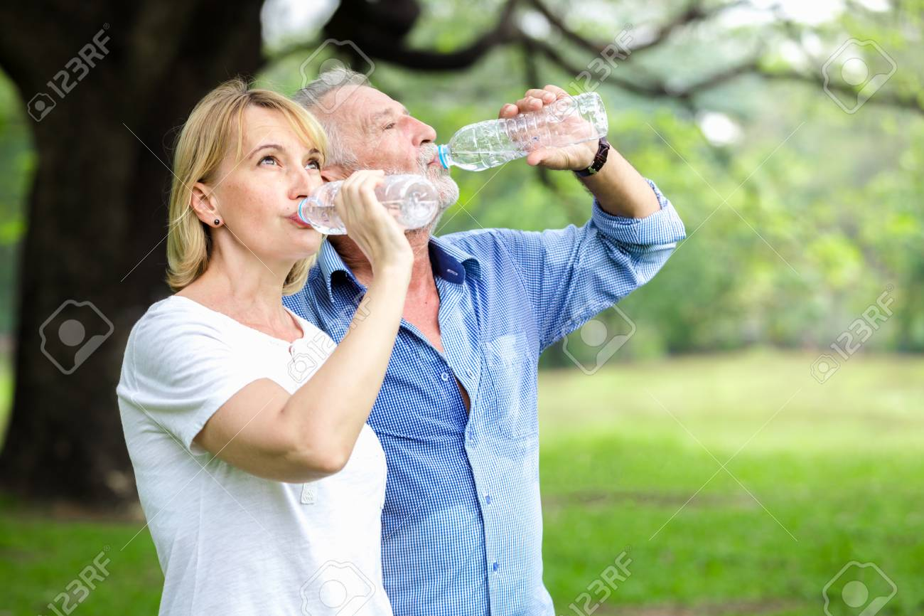 Portrait senior couple standing drinking water at the park - 96513323
