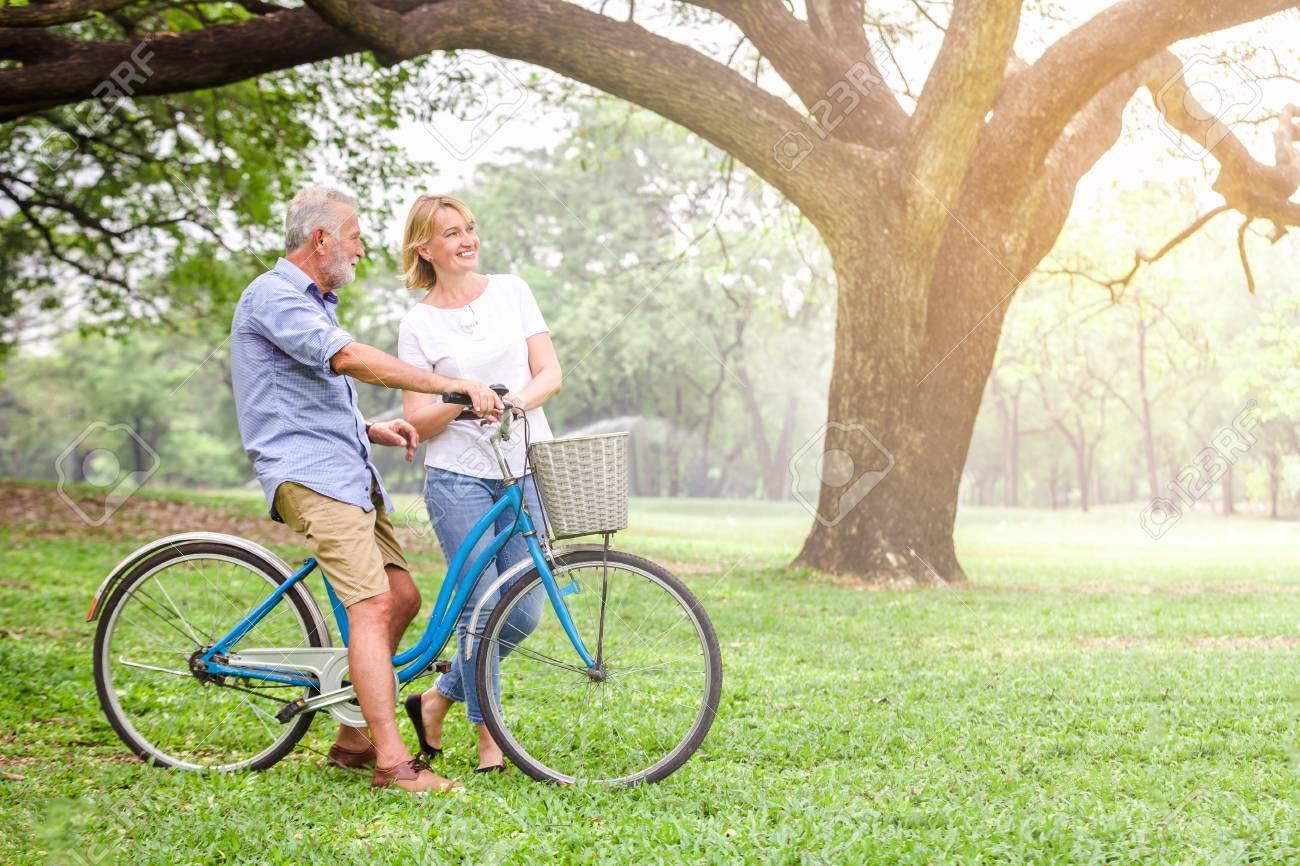 Senior couple walking their bike along happily talking happily. - 98831489