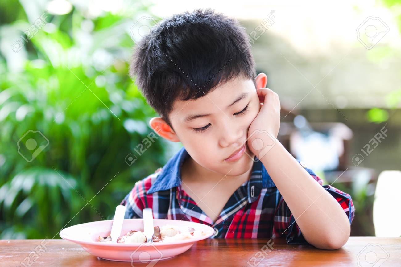 Asian little boy boring eating with rice food on the wooden table - 99408045