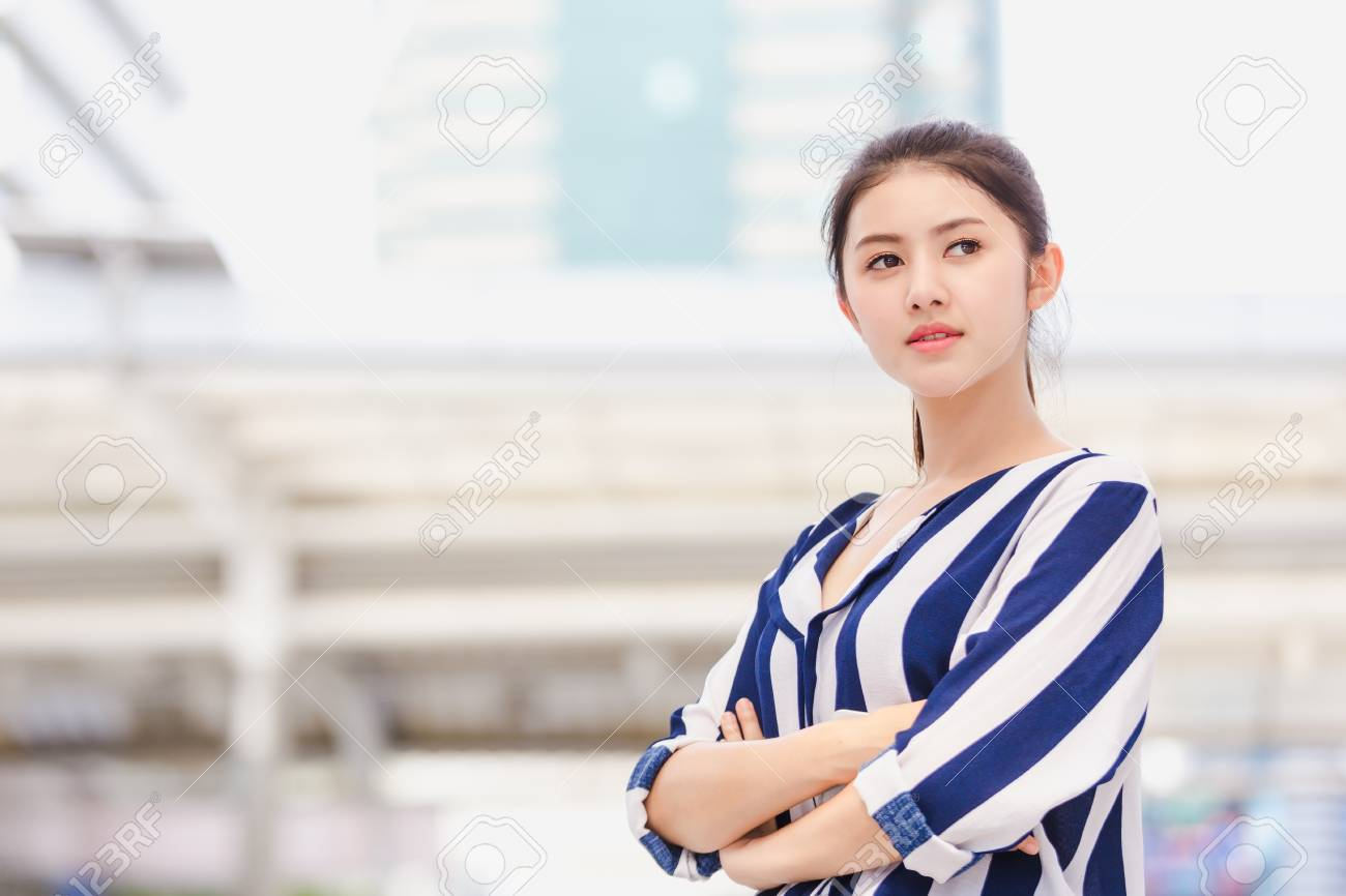 Portrait of smiling pretty lifestyle young business woman standing pointing modern building background - 122269455