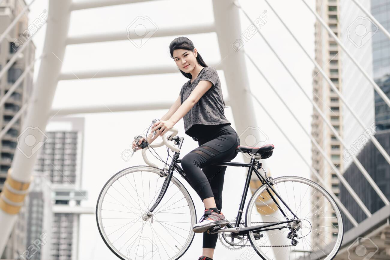 Lifestyle sport woman and health riding bike in city background - 122269772