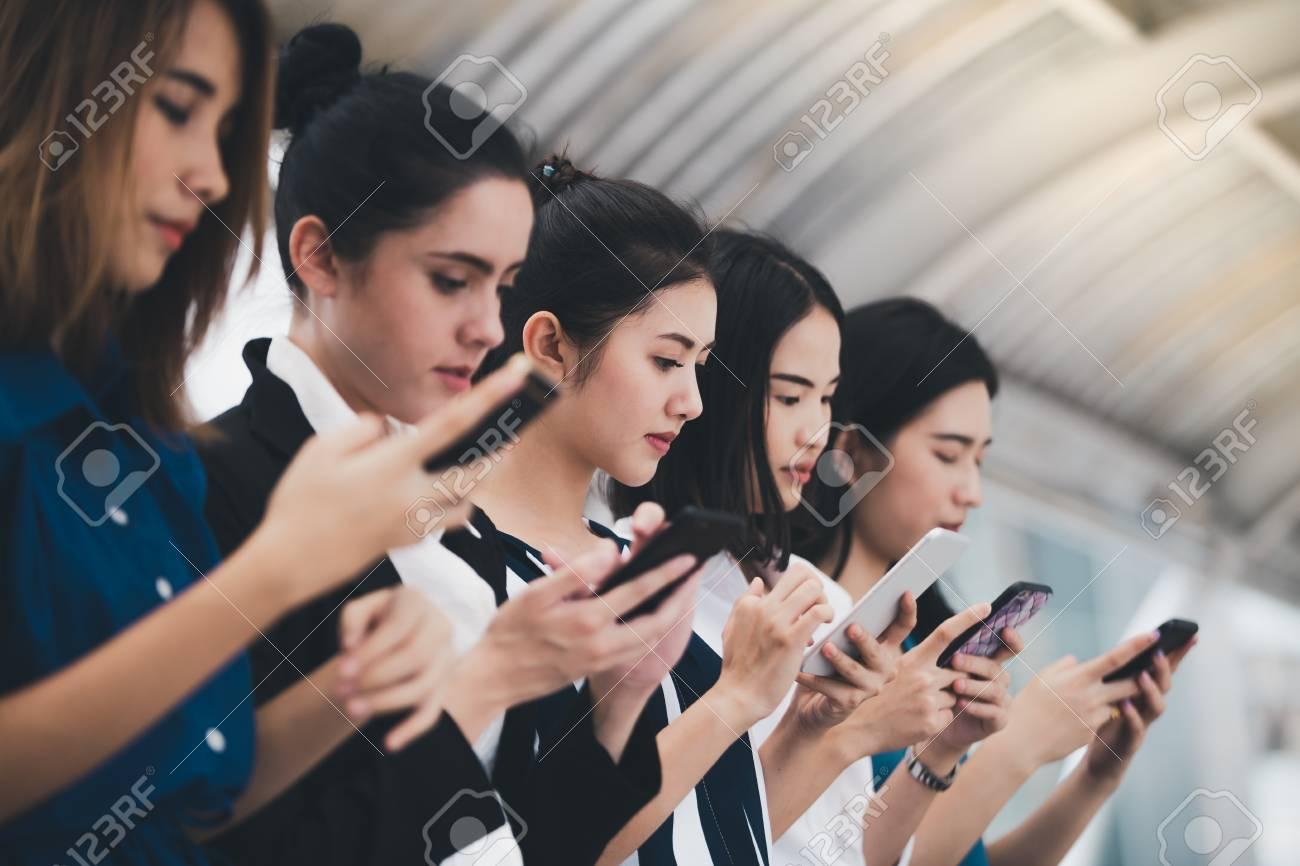 attractive asian businesswomen team playing smartphone outdoor city background - 122269909