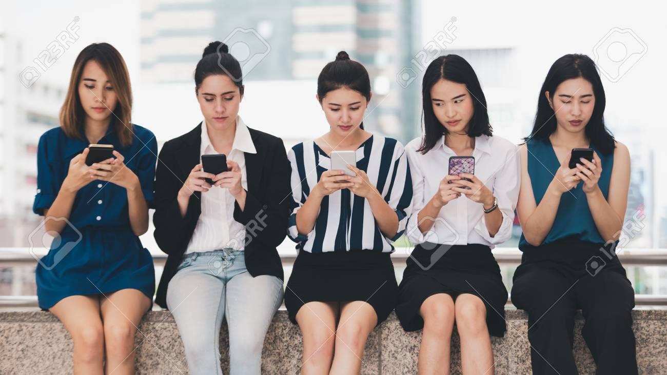 attractive asian businesswomen team playing smartphone outdoor city background - 122269913