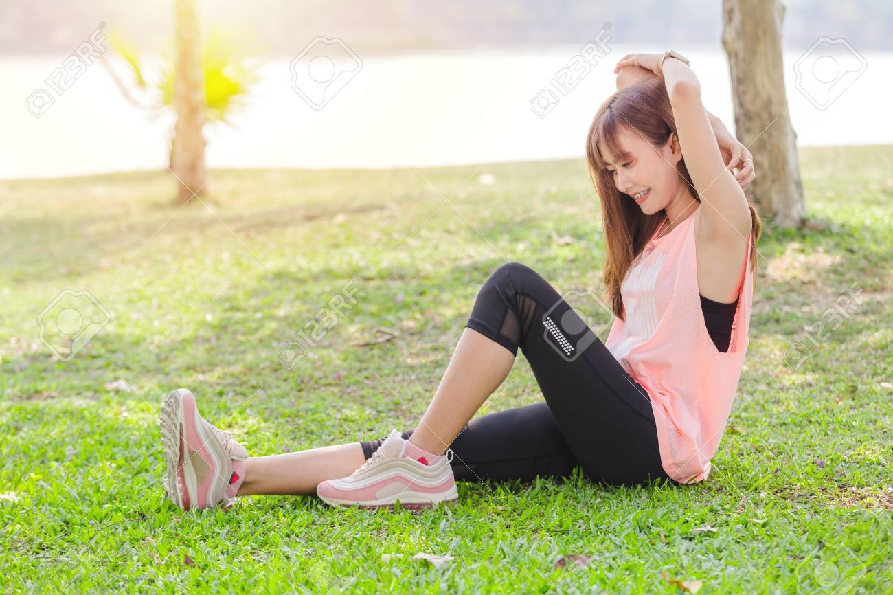 Asian beautiful young woman relaxing excercise in park - 122269917