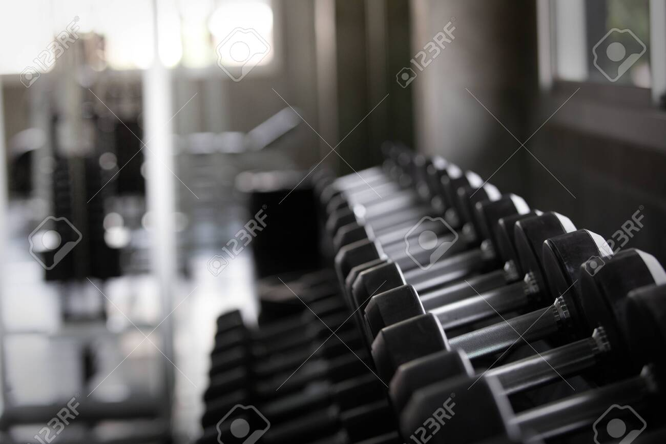 Background view back and white equipment dumbbells on rack in the gym sport center - 122270040