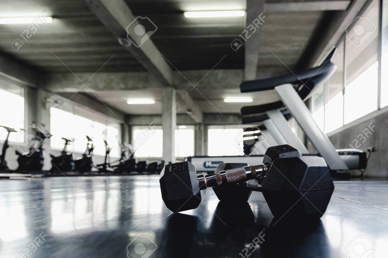 Background view back and white equipment dumbbells on floor in the gym sport center - 122270048