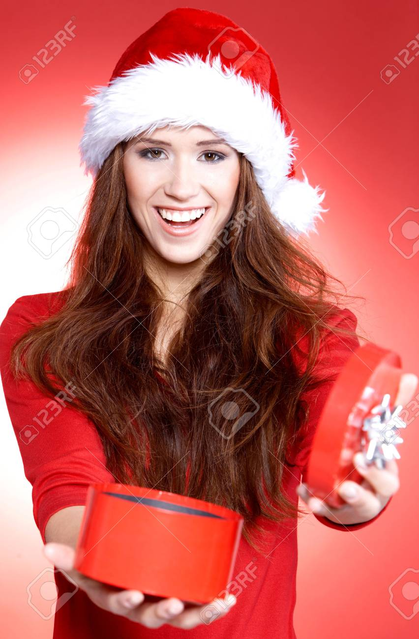 Portrait of beautiful brunette woman wearing santa claus hat on red background Stock Photo - 6006193