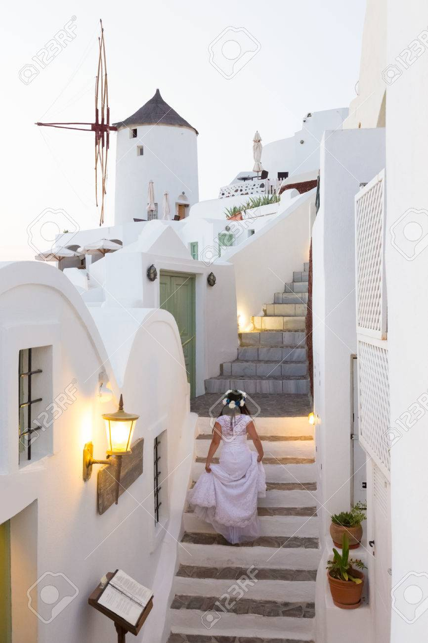 Runaway Bride Ona A Staircase Among Traditional Whitewashed Houses Of Oia  Village On Santorini Island,