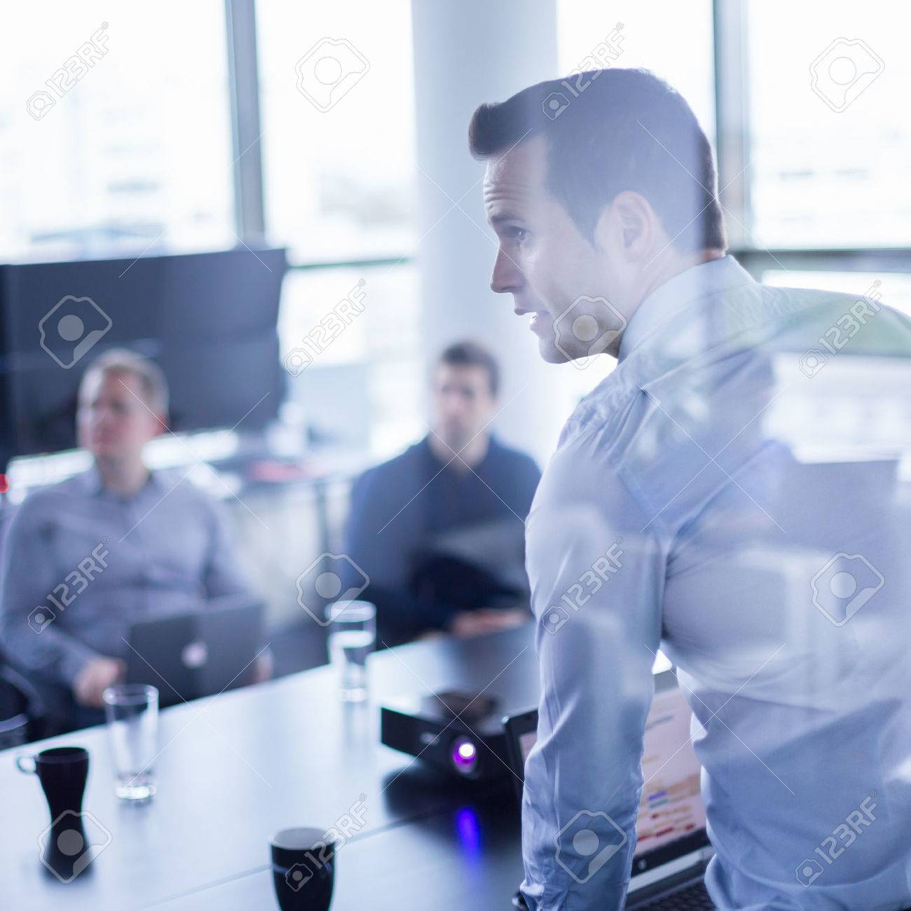 Business man making a presentation at office. Business executive delivering a presentation to his colleagues during meeting or in-house business training, explaining business plans to his employees. - 42193091