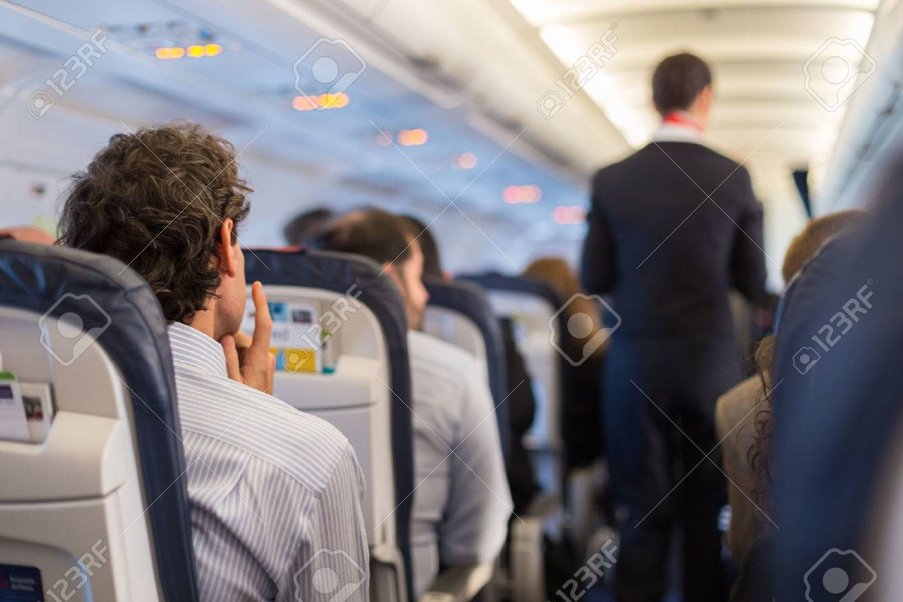 Interior of airplane with passengers on seats and steward walking the aisle. Standard-Bild - 53586633