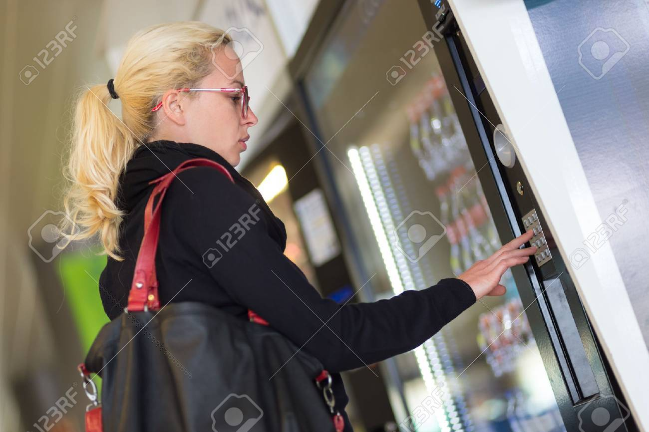 Casual caucasian woman using a modern beverage vending machine. Her hand is placed on the dial pad and she is looking on the small display screen. Standard-Bild - 53607318