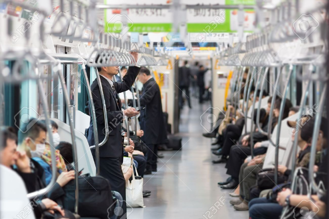 Passengers traveling by Tokyo metro. Business people commuting to work by public transport in rush hour. Shallow depth of field photo. - 53609257
