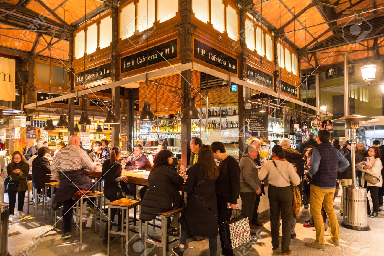 Madrid, Spain - Jan 25, 2016: People eat and drink at Mercado San Miguel on January 25th, 2016 in Madrid, Spain. According to Tripadvisor it is one of top tourist sites in Madrid. - 54764359