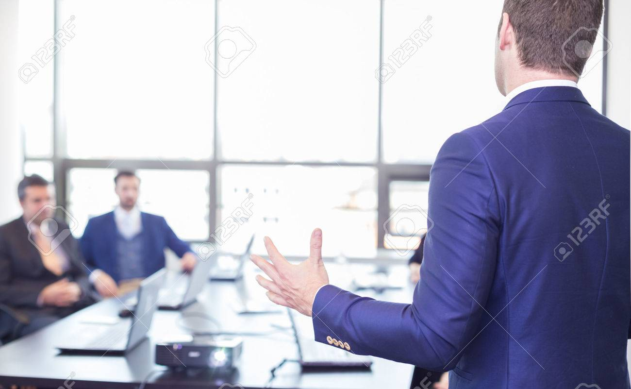 Business man making a presentation in office. Business executive delivering a presentation to his colleagues during meeting or in-house business training, explaining business plans to his employees. Standard-Bild - 54811332