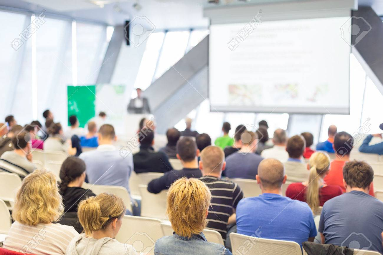 Man giving presentation in lecture hall. Male speeker having talk at public event. Participants listening to lecture. Rear view, focus on people in audience. Standard-Bild - 54764862