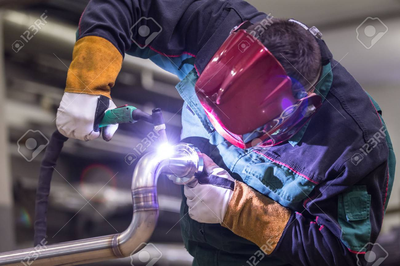 Industrial worker with protective mask welding inox elements in steel structures manufacture workshop. Standard-Bild - 56430609