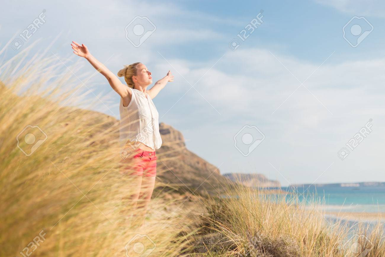 Relaxed woman, arms rised, enjoying sun, freedom and life an a beautiful beach. Young lady feeling free, relaxed and happy. Standard-Bild - 57661725