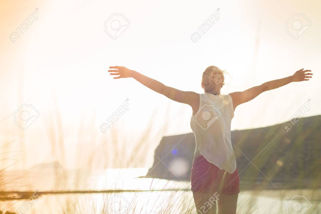 Relaxed woman in white shirt, arms raised, enjoying sun, freedom and life an beautiful beach. Young lady feeling free, relaxed and happy. Concept of vacations, freedom, happiness, joy and well being. Standard-Bild - 61222122