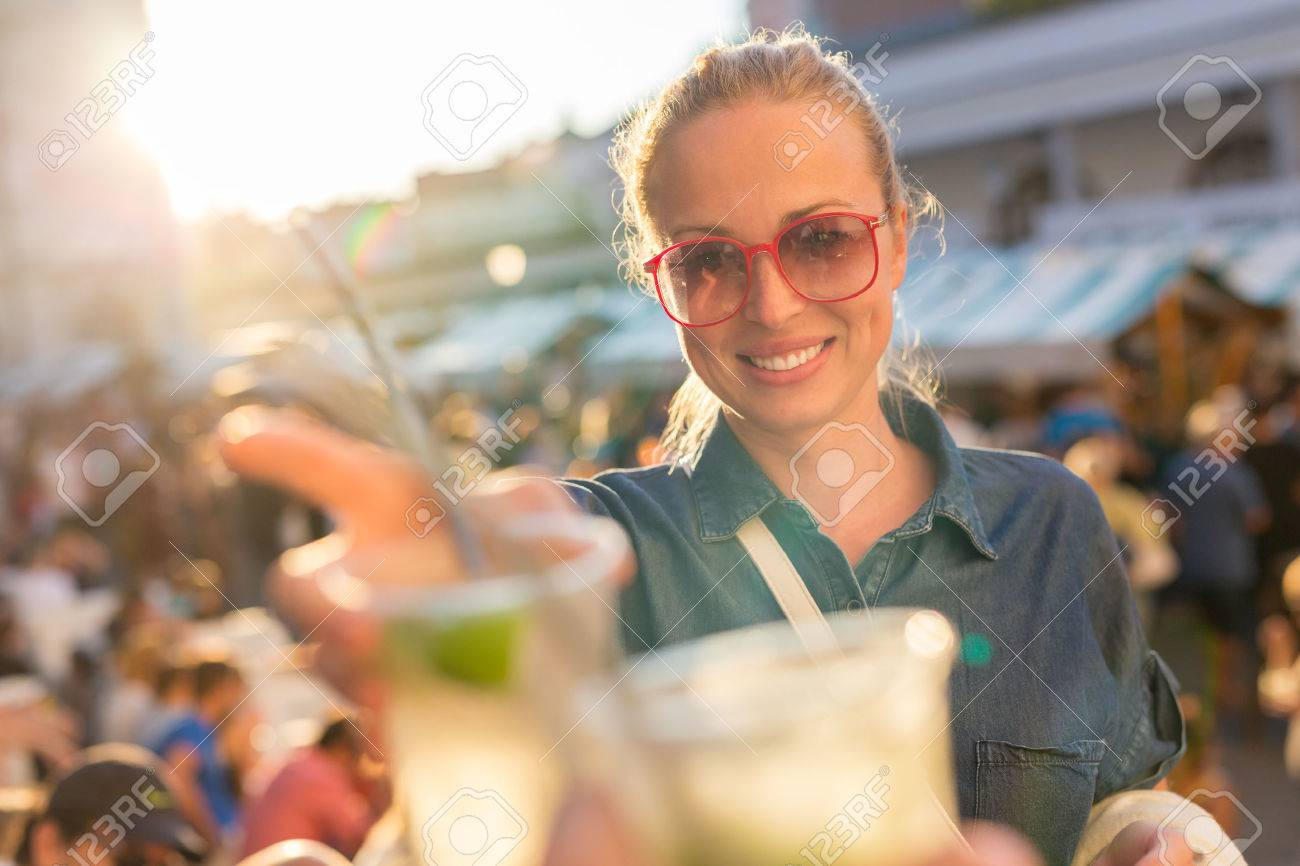 Beautiful young girl toasting outdoors on Open kitchen street food festival in Ljubljana, Slovenia. Popular summer urban tourist event in capital. Standard-Bild - 62299912