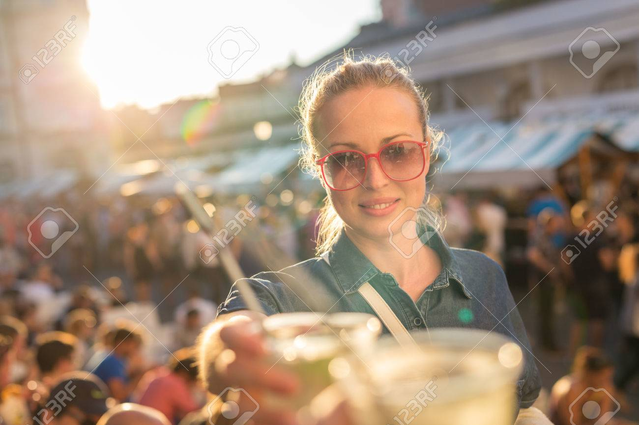 Beautiful young girl toasting outdoors on Open kitchen street food festival in Ljubljana, Slovenia. Popular summer urban tourist event in capital. Standard-Bild - 62299913