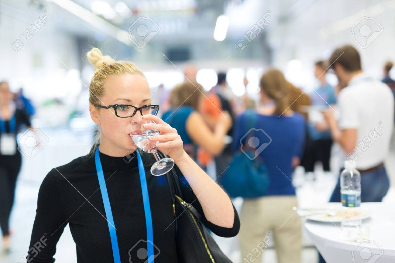Business woman, wearing name tag, drinking glass of water during coffee break at business meeting or conference. Abstract blurred people socializing n background. Standard-Bild - 65702226