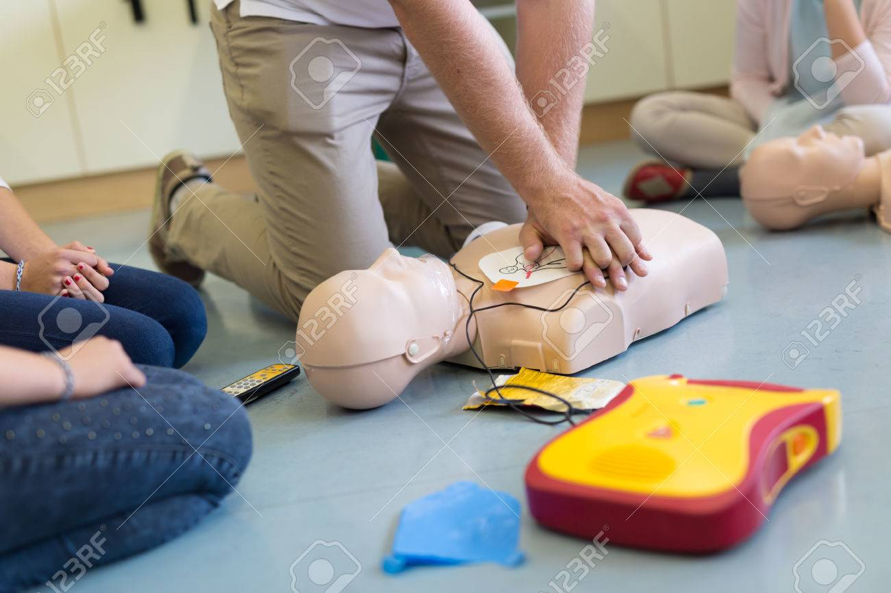 First aid cardiopulmonary resuscitation course using automated external defibrillator device, AED. Standard-Bild - 65018124